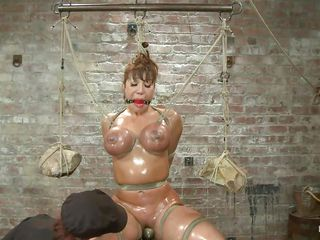 This is a priceless sight! Breasty milf Ava is oiled up and tied hard. Her big boobs are squeezed with rope and at the end of the rope two big and heavy rocks are used as weights to keep it tight. Then her mistress comes..