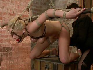 Tied, ball gagged and salivating our sweet blond is roughly fingered from behind. She moans while her pussy is rubbed with a dildo and her ass hole is fisted deeply and merciless. How can such a fragile blond endure such..