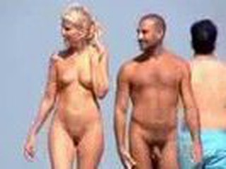 In nature's garb couple filmed walking along the beach, nice blonde with cute tits and shaved pussy.