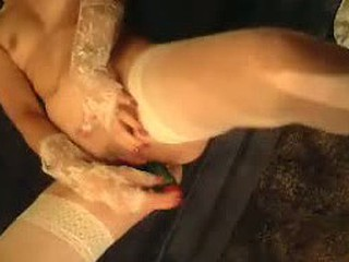 She is really kinky woman: she is clothed in white stockings and fucks herself fast with large green vibrator.