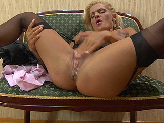Stacked blond in glasses parts her stockinged legs to finger fuck her box
