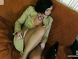 Elegant business-lady in sheer tights taking up a sex-toy in advance of a real thing