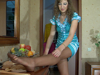 Cute honey takes out a pair of fine tan hose adjusting 'em on her lengthy legs